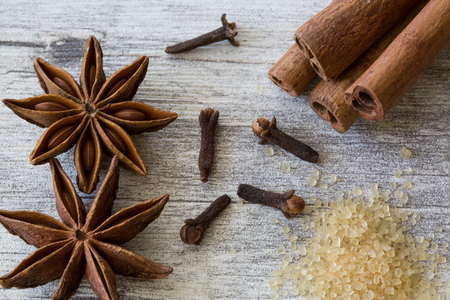 Anise stars, cinnamon rolls, cloves and brown cane sugar on grey wooden rustic background, close up, macro. Фото со стока