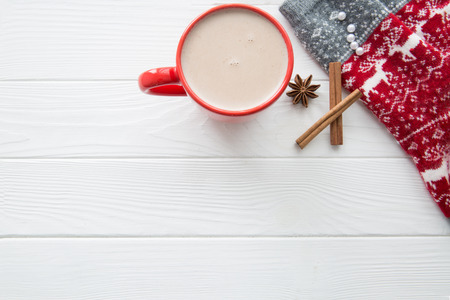Hot cocoa with spices:cinnamon and anise stars and christmas ornament socks on white wooden background. Top view, copy space for greeting.