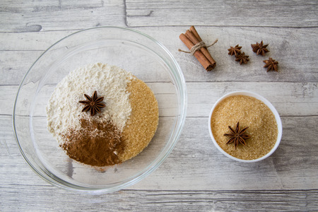 Ingredients for making christmas pie, cakes and cookies on grey wooden table background. Anise stars, cane sugar, cinnamon, flour, natural vanilla  and nutmeg mixes in the big glass bowl. Imagens