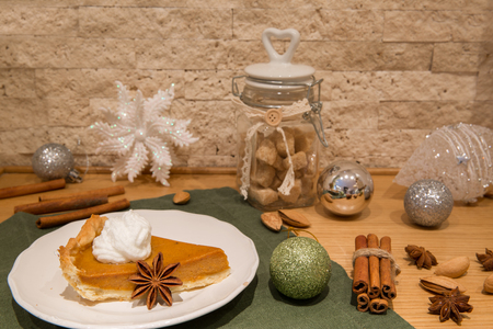 Christmas american pumpkin pie with whipped cream, cinnamon and cloves. Decorations of silver and green christmas balls.