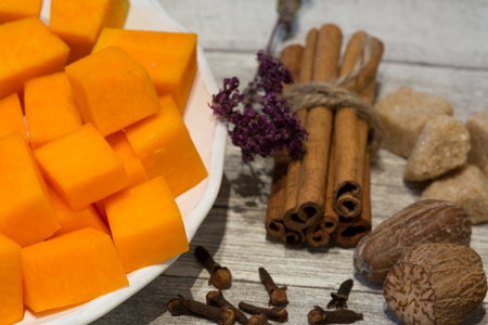 Chopped pumpkin on white plate with cinnamon sticks, anise star, nutmeg and cloves on grey wooden table background. Ingredients for baking tasty pie or cupcakes.