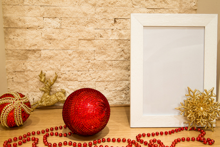 Christmas decoration, mock up. Golden snowflake, deer and christmas ball with paillette and spangle, red beads and christmas toys on brock wall background. Free space, copy space. Banque d'images