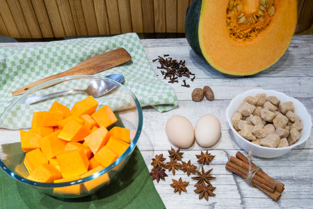 Fresh pumpkin (squash) on kitchen table with baking ingredients for cooking. A lot of spice, nuts and eggs, cane brown sugar. Foto de archivo