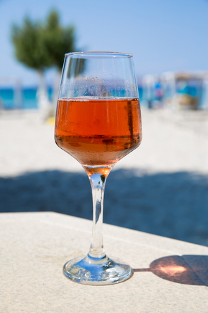 One glass of cold rose wine served on the beach with beautiful sea view. Relax concept. Bright sunny day with blue sky.