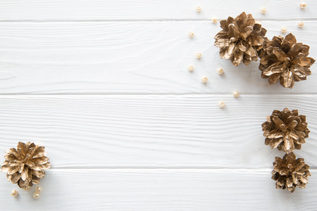 Heap of golden pine cones (painted fir cones) and placer of beige beads on white rustic background, top view, copy space. Christmas background for greeting. Foto de archivo - 111260037