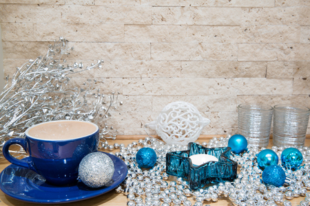 Hot cacao with milk in blue cup. Silver and blue Christmas decorations, like silver beads and Christmas balls. Turquoise and silver candlesticks.