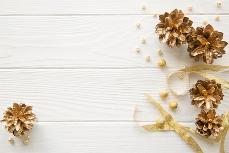 Golden pine cones and golden sparkling ribbon, yellow and beige beads on white wooden background. Free space for text. Top view. Christmas background.