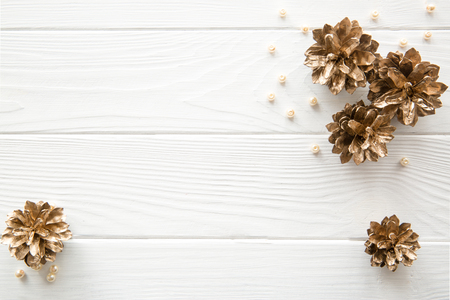 Golden pine cones and beads on white wooden background. Space for text. Top view. Christmas background.
