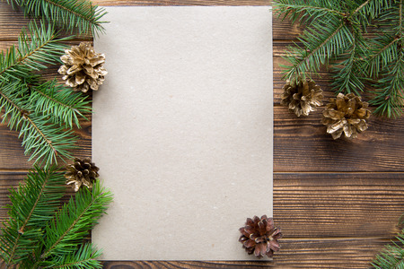 Golden cones and fir three branches on brown wooden table background. Mock up, free space for text. Copy space.