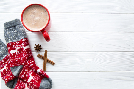 Red socks with Christmas ormanent and deer. Hot chocolate with milk in red cup with spices: anise stars and cinnamon  on white wooden table. Top view. Free space for text. White wooden background. Stock Photo