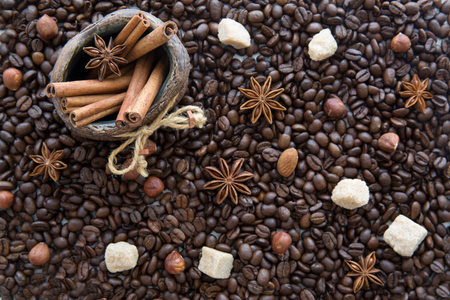 Christmas coffee beans background. Decorative jug with cinnamon sticks, almonds, anise and cane sugar. Top view.