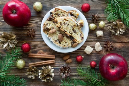 Traditional Christmas stollen cake. German festive dessert on brown wooden table background. Red apples, Christmas candy stick and red sparkling christmas balls.