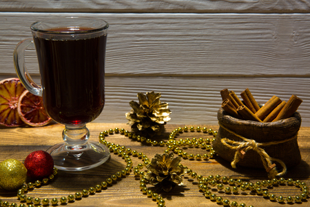Mulled wine on brown wooden table, golden and red sparkling Christmas balls decorations. Stock Photo