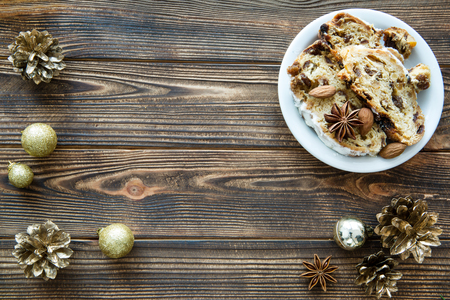 Traditionla Christmas cake on brown wooden table. Golden Christmas decorations, pine cones and sparkling balls. Space for text. Copy space. Standard-Bild