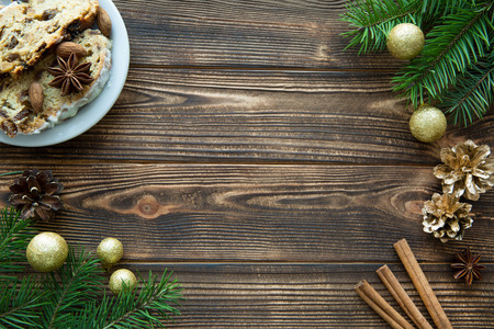 Christmas holiday mood background, traditional Christmas cake, golden Christmas balls and golden cones, fir tree branches decorations on brown wooden table. Copy space.