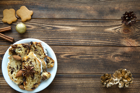 Christmas cake and gingerbread cookies on brown wooden table background. Christmas golden decorations, pine cones, sparkling golden balls. Space for text. Copy space. Standard-Bild