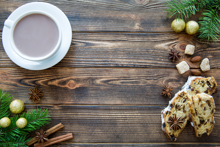 A cup of hot cocoa on brown wooden table, a traditional Christmas cake, golden Christmas decorationas and fir tree branches. Space for text. Copy space.