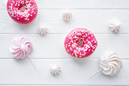 Tasty doughnuts and pink and white delicious meringues on white background. Zdjęcie Seryjne