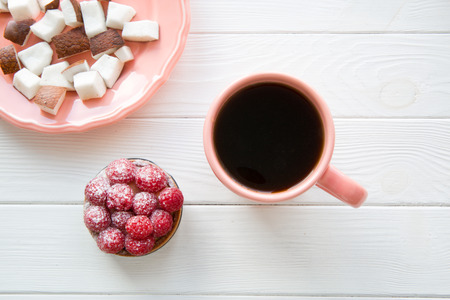 Healthy sweets and pink plate and a cup of coffee on white table background, top view.