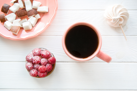 Living coral color cup and plate on white table background. Coconut pieces and raspberry tart and merengue, top view.