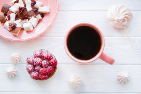 Healthy snack, coconut pieces, tasty raspberry cake and meringue on white wooden table background. A cup of black coffee.