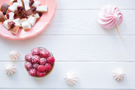 Pink merengue, raspberry cake and coconut on living coral color on white wooden table. Copy space for text.