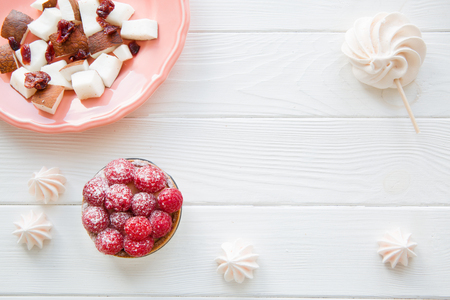 Healthy sweets on white wooden table. Coconut pieces, merengua and berry tart. Space for text, copy space.