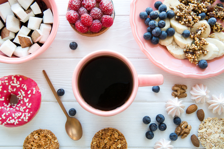 Stylish served table with healthy organic food, tasty doughnut and raspberry cake. Banana and coconut pieces, granola and little merengue. Pink and coral living color plate and cup.