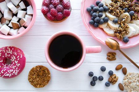 Trendy served table with healthy food, tasty pink doughnut and low fat cookies. Banana and coconut pieces, granola and little merengue. Pink color plates and cup.