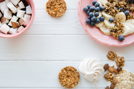 Healthy tasty snack on white wooden table, copy space for text. Fruit pieces in coral color plates, natural cookies with oat and nuts.