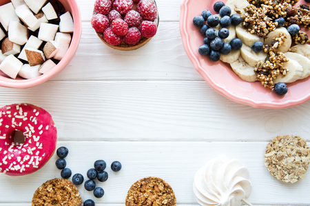 Served table, healthy breakfast: granola with fresh blueberry and banana. Coconut pieces in coral color plates on white wooden table. Space for text. Stock Photo