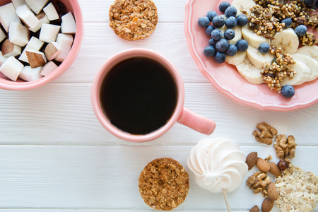 A cup of fresh black coffee, healthy bran cookies with pieces of coconut and banana on white wooden table background. Top view.