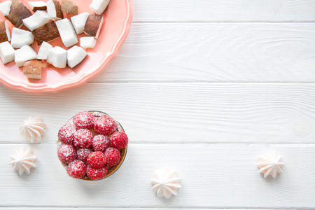 A coconut pieces in coral living plate, vegetarian sweets on white table background. Copy space, free space for text.