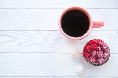 A cup of black tea and tasty desserts, little merengues and fruit raspberry tart on white wooden table background, space for text. Stock Photo