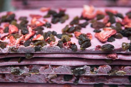 Tasty homemade chocolade with dried fruits like strawberry and raisins, close up. Pink chocolate. Stockfoto