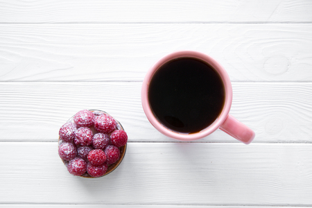Tasty raspberry cake and a cup of coffee on white wooden table, top view. Space for text, copy space.