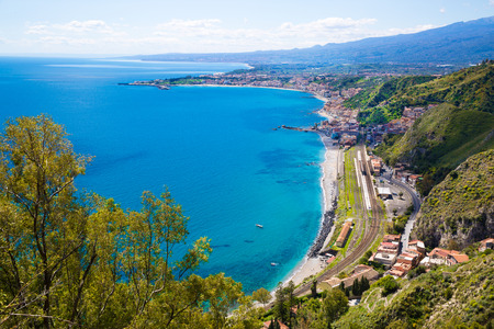 Sicily, Italy. Beautiful panoramic view to Etna volcano and Mediterranean sea (Ionian sea). Bright turquoise waters on summer sunny day.
