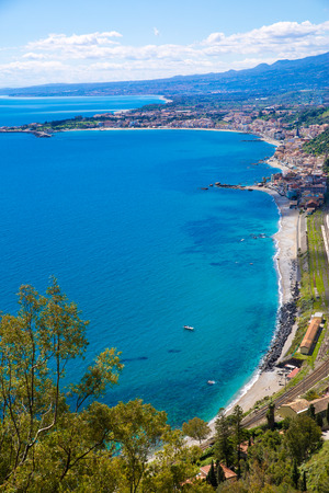 Panoramic view to Etna volcano in Taormina, Sicily island, Italy. Mediterranean sea (Ionian sea). Bright turquoise waters on summer sunny day.