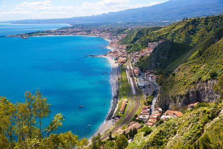 Mediterranean sea coastline, luxury resort in Taormina, Sicily island, Italy. Clear waters of Ionian sea near Etna Volcano. Aerial view.
