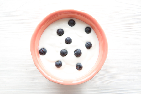 White yogurt with blueberry inliving coral color bowl on white wooden table. Free copy space for text. Imagens - 121937354