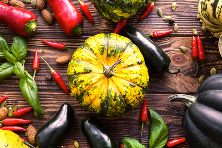 Bright autumn harvest, assortment of fresh vegetables, different kinds of squash and pumpkins on brown background. Top view.
