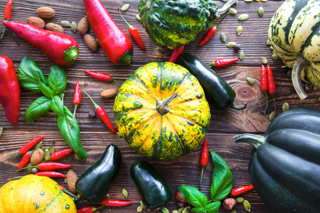 Colorful fall vegetables, assortment of pumpkins, squash and green and red paprika on brown rustic table, top view.