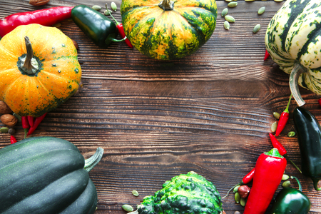 Assortment of squash and pumpkins autumn background. Free copy space for text and greetings on brown rustic table, top view. Bright autumn colors.
