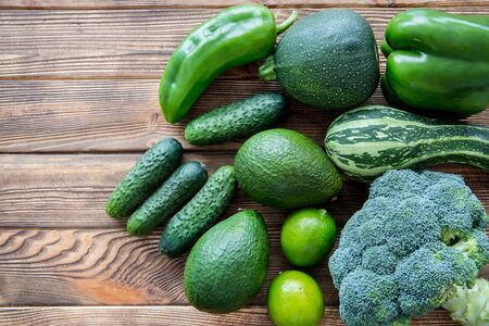 Fresh green vegetables and fruits on wooden table background, top view. Assortment of veg. Bright colors. Stock Photo