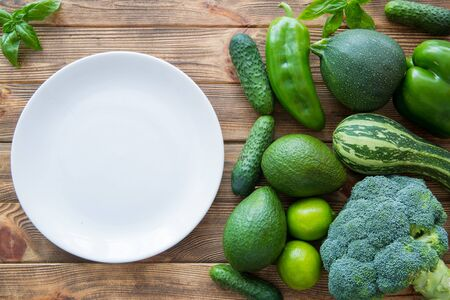 Fresh green vegetables and fruits on wooden table background, top view. Big white plate, copy space. Diet concept or healthy food.