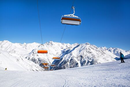 Ski lifts in the Alp mountains, Tirol, Austria. Bright blue sky and mountain covered with snow.