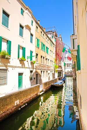 Amazing view to the narrow canal in Venice, Italy. Old buildings reflect in green canal water.