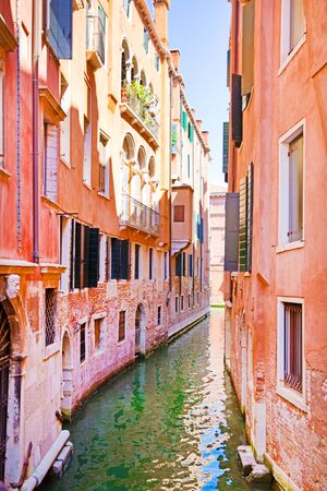 Beautiful  canal in Venice, Italy. Old colorful pink and orange buildings and bright green water.