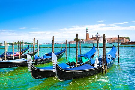 Gondolas and bright turquoise water of canal. Grand Canal in Venice, Italy. Sunny summer vacations. Beautiful landscape with bright colors.
