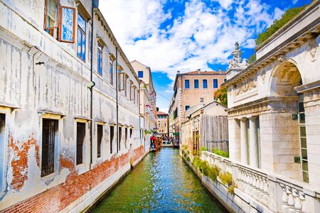 Narrow canal in Venice, Italy. Old historical buildings and bright green water. Bright blue sky. 写真素材